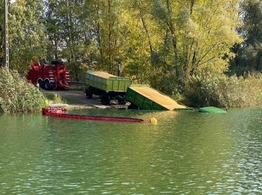 Ciągnik i przyczepy z kukurydzą w jeziorze